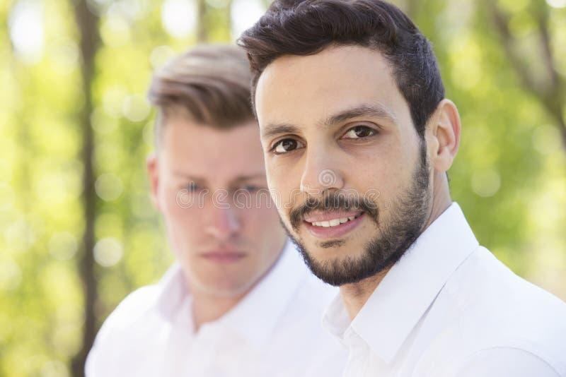 Δύο ανθρώπων στην άσπρη στάση πουκάμισων εξωτερική και το χαμόγελο στη κάμερα στοκ φωτογραφία