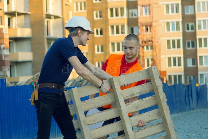Δύο ανθρώπων τακτοποιώντας παλέτες σε μια αποθήκη εμπορευμάτων στοκ φωτογραφίες