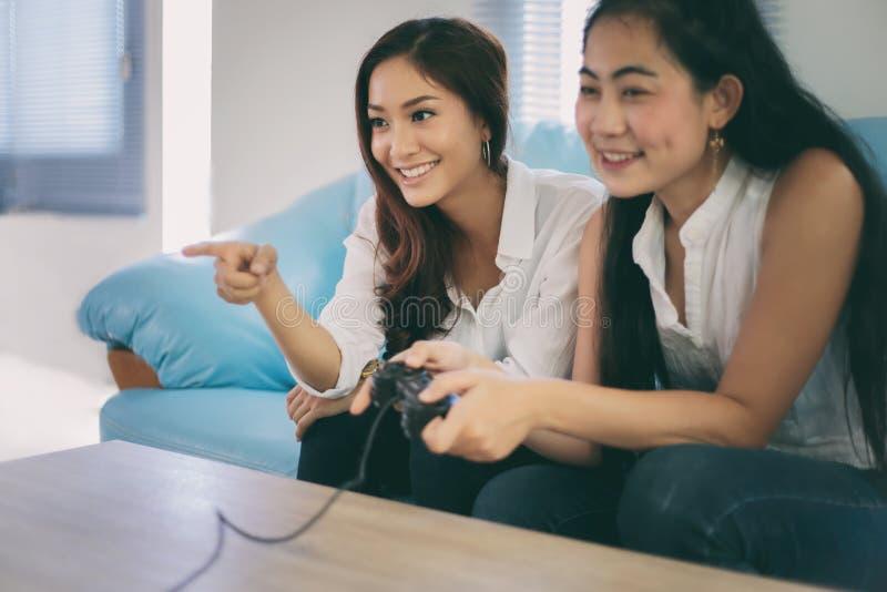Δύο ανταγωνιστικοί φίλοι γυναικών που παίζουν τα τηλεοπτικά παιχνίδια και το συγκινημένο εκτάριο στοκ φωτογραφία με δικαίωμα ελεύθερης χρήσης