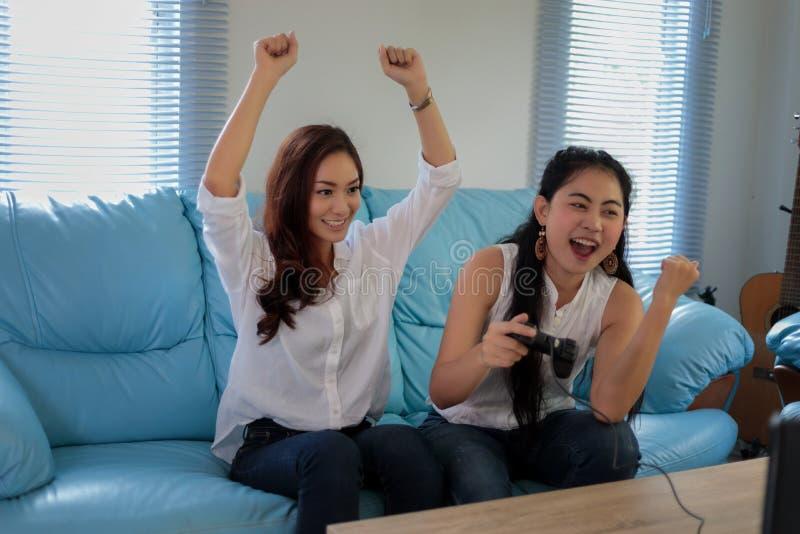 Δύο ανταγωνιστικοί φίλοι γυναικών που παίζουν τα τηλεοπτικά παιχνίδια και το συγκινημένο εκτάριο στοκ εικόνες με δικαίωμα ελεύθερης χρήσης