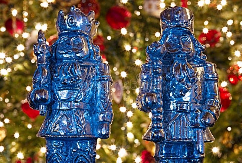 Δύο αντιπροσωπεύσεις καρυοθραύστης μετάλλων μπροστά από ένα αναμμένο χριστουγεννιάτικο δέντρο στοκ εικόνα με δικαίωμα ελεύθερης χρήσης