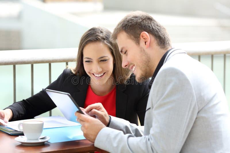 Δύο ανώτεροι υπάλληλοι που συμβουλεύονται τα σε απευθείας σύνδεση στοιχεία στοκ εικόνες