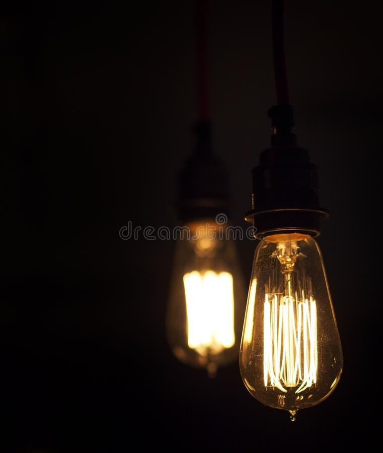 Δύο απομονωμένες εκλεκτής ποιότητας καμμένος λάμπες φωτός ύφους που κάποια είναι στοκ εικόνα