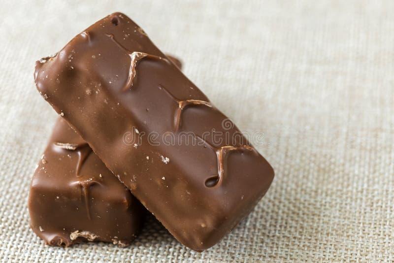 Δύο απομονωμένοι απομονωμένοι σκοτεινοί καφετιοί snickers καραμελών σοκολάτας φραγμοί στο ελαφρύ αντίγραφο υφασμάτων καμβά χωρίζο στοκ φωτογραφία με δικαίωμα ελεύθερης χρήσης