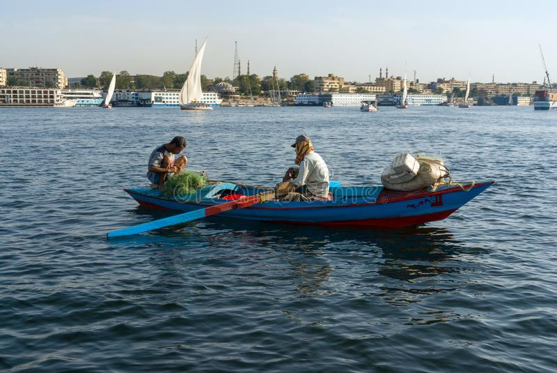 Δύο αραβικοί ψαράδες σε μια μικρή βάρκα χαρακτηριστική του ποταμού του Νείλου, ένας που κωπηλατεί και άλλος που σκύβει στοκ εικόνα με δικαίωμα ελεύθερης χρήσης