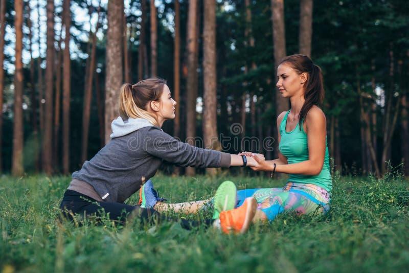 Δύο αρκετά θηλυκοί φίλοι που ασκούν τη γιόγκα που κάνει μαζί το ευρύ πόδι κάθισαν την μπροστινή κάμψη υπαίθρια στοκ φωτογραφία