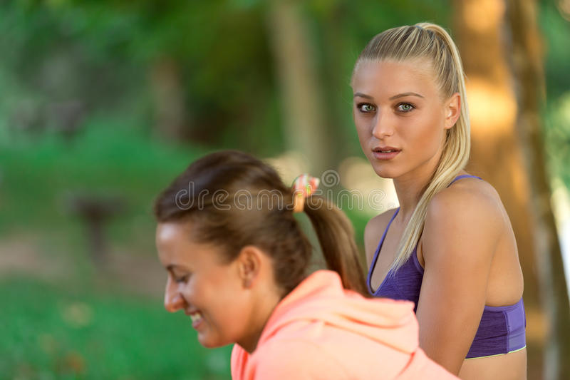 Δύο αρκετά νέα γυναίκα στη φίλαθλη εξάρτηση που χρησιμοποιεί ένα smartphone στοκ εικόνες