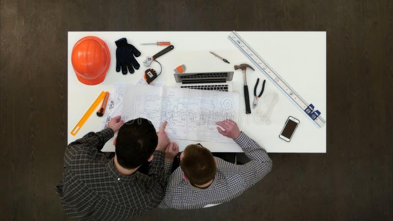 Δύο αρσενικοί αρχιτέκτονες που συζητούν τα σχέδια και τα σχεδιαγράμματα στοκ φωτογραφία