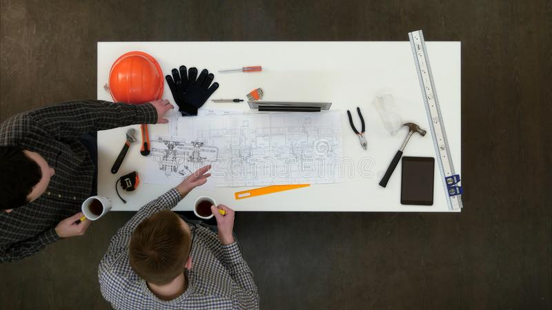 Δύο αρσενικοί αρχιτέκτονες που συζητούν τα σχεδιαγράμματα που πίνουν τον καφέ στοκ εικόνα
