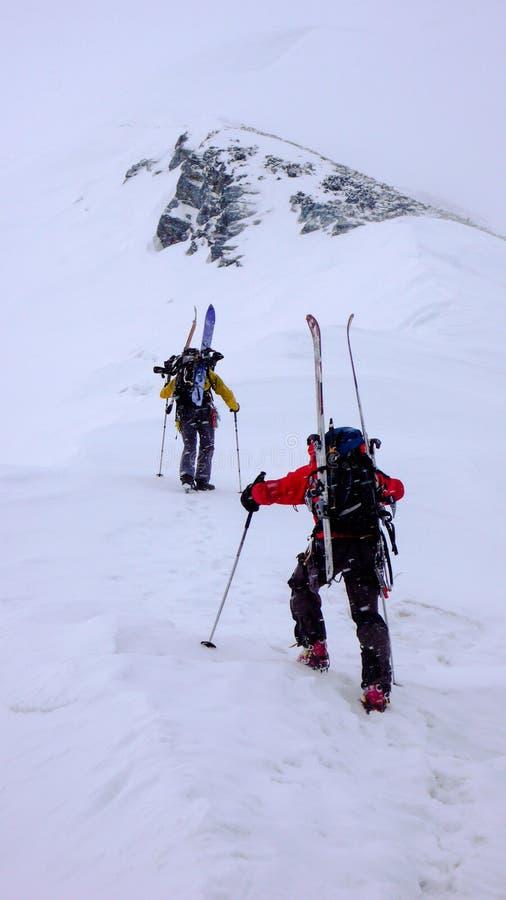 Δύο αρσενικοί ορειβάτες βουνών σε έναν backcountry γύρο ορειβασίας σκι στο άσχημο καιρό στοκ φωτογραφία
