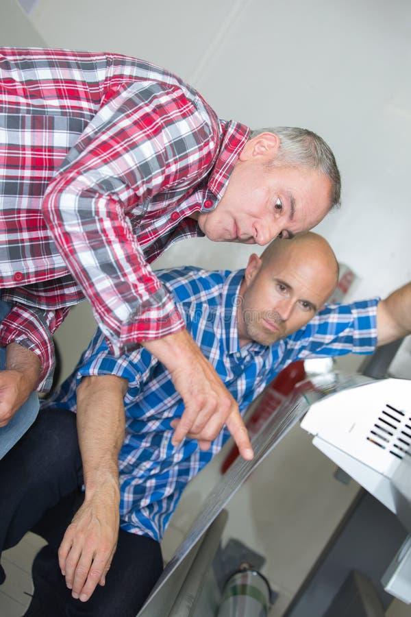 Δύο αρσενικοί τεχνικοί που επισκευάζουν τη μηχανή στοκ φωτογραφία με δικαίωμα ελεύθερης χρήσης