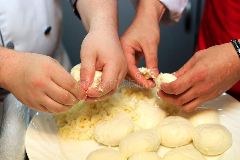 Δύο αρχιμάγειρες που κόβουν επάνω το τυρί μοτσαρελών στοκ εικόνες