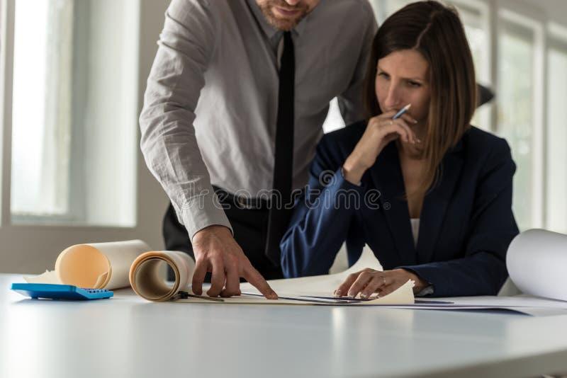 Δύο αρχιτέκτονες που συζητούν ένα σχέδιο ή ένα σχεδιάγραμμα στοκ εικόνα