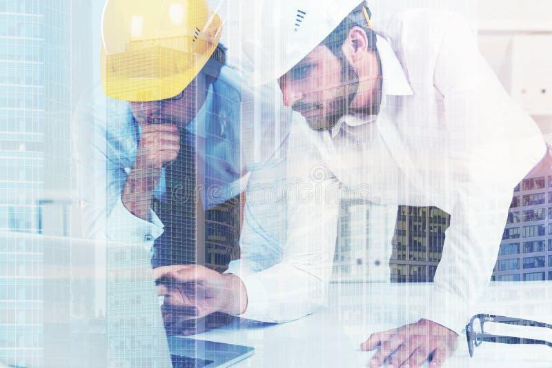 Δύο αρχιτέκτονες hardhats σε ένα γραφείο, διπλάσιο στοκ εικόνες