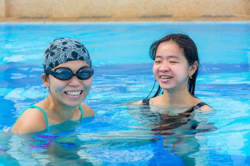 Δύο ασιατικά κορίτσια έχουν τη διασκέδαση στην πισίνα στοκ φωτογραφία με δικαίωμα ελεύθερης χρήσης