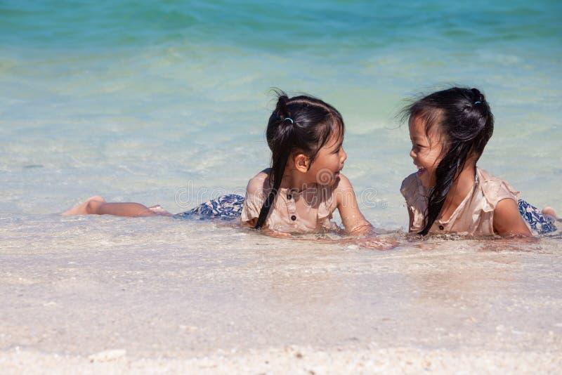 Δύο ασιατικά κορίτσια παιδιών που έχουν τη διασκέδαση για να παίξει το νερό στην όμορφη θάλασσα μαζί στις θερινές διακοπές στοκ φωτογραφία με δικαίωμα ελεύθερης χρήσης