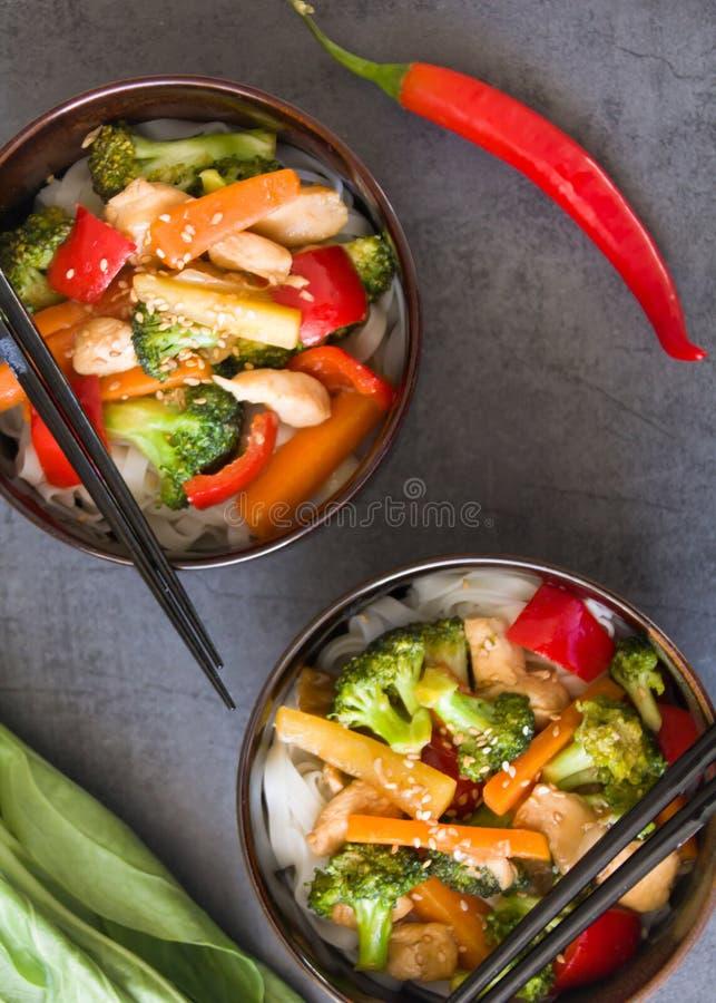 Δύο ασιατικά πιάτα με το κοτόπουλο, το μπρόκολο, το κόκκινο πιπέρι & τα νουντλς ρυζιού Ανακατώστε & πιάτο τηγανητών στο σκοτεινό  στοκ φωτογραφίες