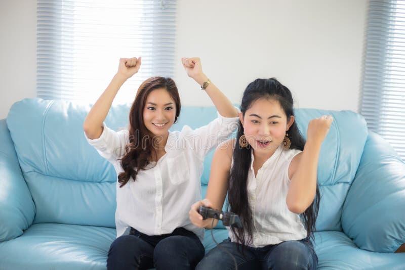 Δύο ασιατικοί ανταγωνιστικοί φίλοι γυναικών που παίζουν τα τηλεοπτικά παιχνίδια και το exci στοκ φωτογραφίες με δικαίωμα ελεύθερης χρήσης