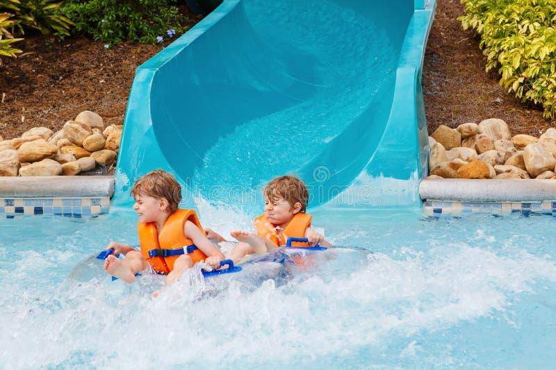 Δύο αστεία συγκινημένα παιδιά που απολαμβάνουν τις θερινές διακοπές στο λούνα παρκ νερού που οδηγά στη φωτογραφική διαφάνεια με τ στοκ φωτογραφία
