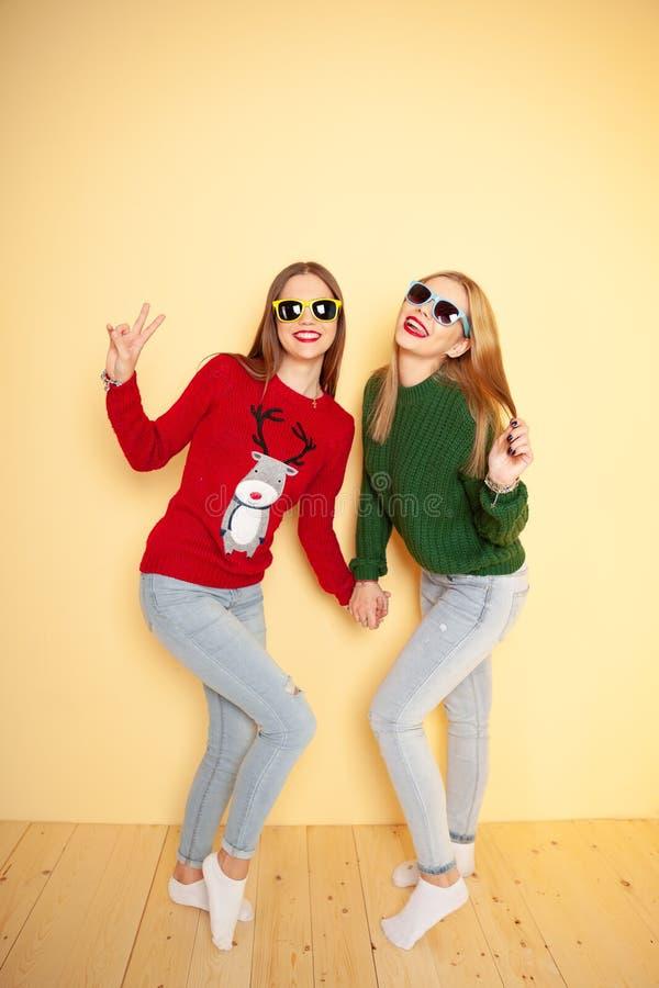 Δύο αστεία όμορφα κορίτσια hipster στα πουλόβερ και τα γυαλιά ηλίου Χειμώνας και μόδα έννοιας στοκ φωτογραφίες