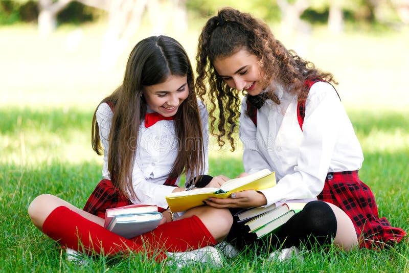 Δύο αστείες μαθήτριες κάθονται στη χλόη και διαβάζουν τα βιβλία Τα κορίτσια, φίλες, αδελφές διδάσκουν τα μαθήματα στη φύση στοκ εικόνες