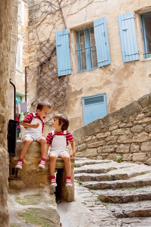 Δύο λατρευτά παιδιά, που κάθονται στο βράχο οδών, χαμόγελο, που τρώει το ι στοκ εικόνα με δικαίωμα ελεύθερης χρήσης