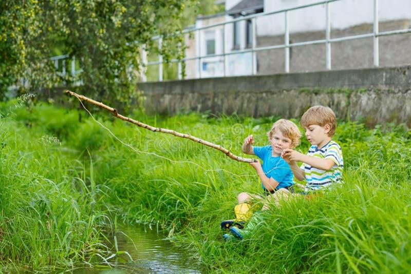 Δύο λατρευτοί μικροί φίλοι που αλιεύουν με τη ράβδο selfmade στοκ εικόνα με δικαίωμα ελεύθερης χρήσης