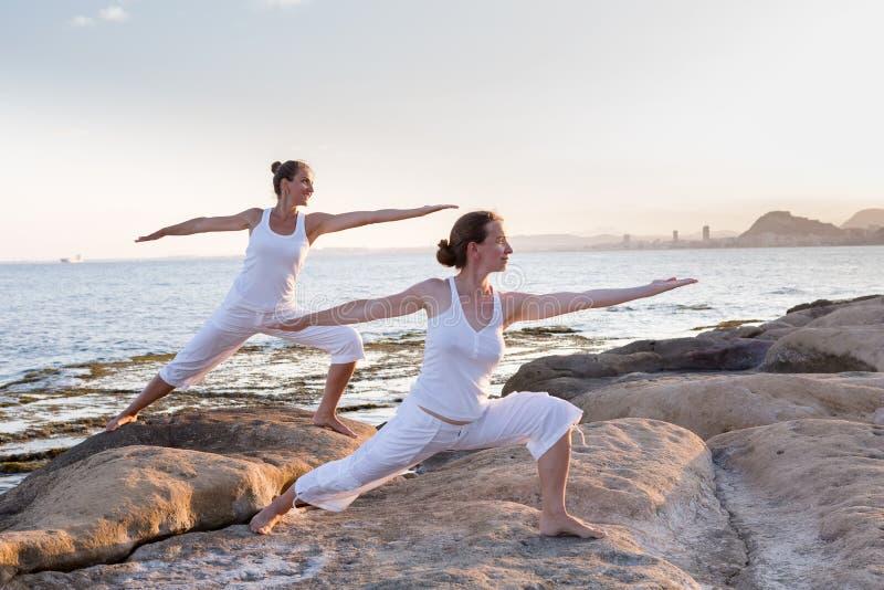Δύο αδελφές κάνουν τις ασκήσεις γιόγκας στην ακτή στοκ φωτογραφία