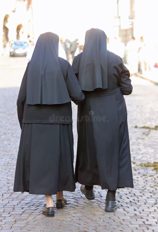 Δύο αδελφές με τα μαύρα φορέματα και ένα πέπλο που περπατά στην πόλη στοκ εικόνες