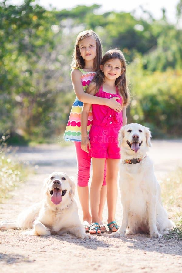 Δύο αδελφές σε έναν περίπατο με τα σκυλιά στο πάρκο στοκ εικόνες