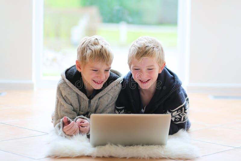 Δύο αδελφοί που βρίσκονται στο πάτωμα με το lap-top στοκ εικόνες με δικαίωμα ελεύθερης χρήσης