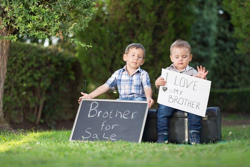 Δύο αδελφοί που θέτουν με τους πίνακες σημαδιών στοκ φωτογραφία