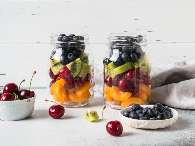 Δύο βάζα γυαλιού με τα μούρα και τα φρούτα Σαλάτα φρούτων με τα βερίκοκα, το ακτινίδιο, τα κεράσια και τα βακκίνια στα βάζα γυαλι στοκ εικόνες με δικαίωμα ελεύθερης χρήσης