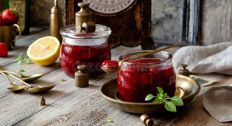 Δύο βάζα γυαλιού με τη σπιτική κονσερβοποιημένη φράουλα φράσσουν, μαρμελάδα, ζελατίνα στον αγροτικό ξύλινο γκρίζο πίνακα με το βα στοκ εικόνες