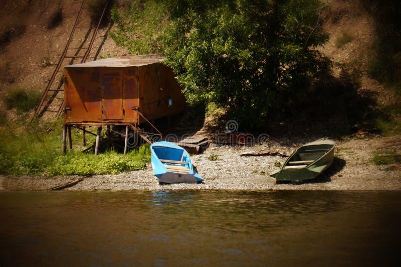 Δύο βάρκες στην όχθη ποταμού κοντά σε ένα μεγάλο γκαράζ μετάλλων στοκ εικόνες