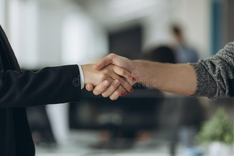 Δύο βέβαια χέρια τινάγματος επιχειρησιακών ατόμων κατά τη διάρκεια μιας συνεδρίασης στο γραφείο, την επιτυχία, τη συναλλαγή, το χ στοκ εικόνα με δικαίωμα ελεύθερης χρήσης