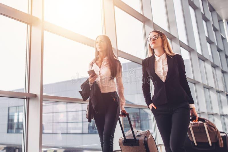 Δύο βέβαιες επιχειρηματίες που φέρνουν τις βαλίτσες στον αερολιμένα στοκ φωτογραφία