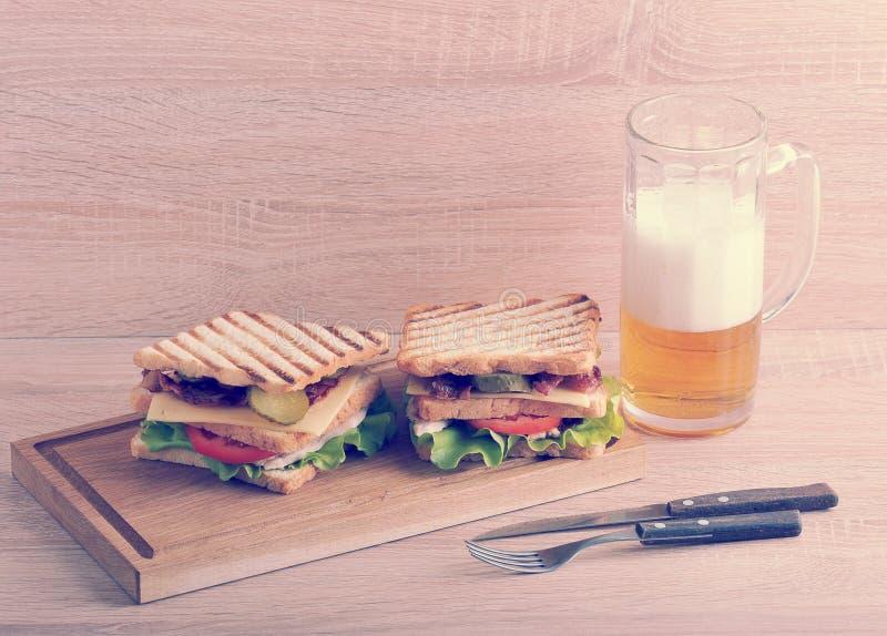 Δύο βαλμένο σε στρώσεις σάντουιτς με το στήθος μπέϊκον και κοτόπουλου σε ένα ξύλινο Β στοκ εικόνες