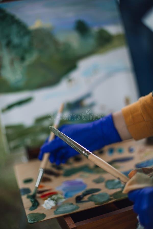 δύο βούρτσες στα χέρια του καλλιτέχνη στοκ φωτογραφία με δικαίωμα ελεύθερης χρήσης
