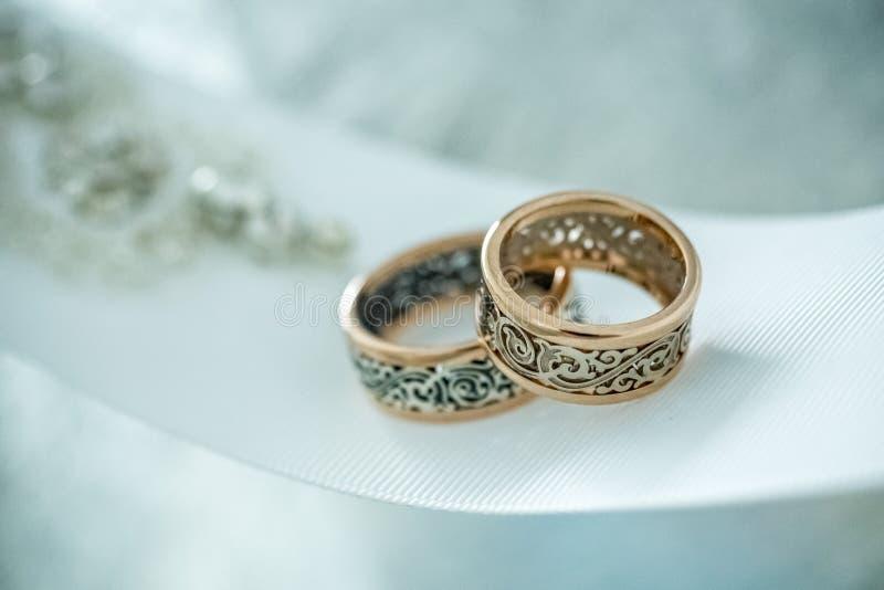 Δύο γαμήλια δαχτυλίδια με το σπάνιο σχέδιο στην άσπρη ευρεία κορδέλλα στοκ φωτογραφία με δικαίωμα ελεύθερης χρήσης