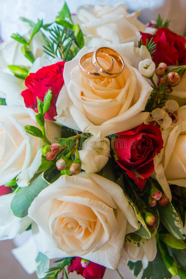 Δύο γαμήλια χρυσά δαχτυλίδια με τα διαμάντια είναι στο bride& x27 ανθοδέσμη του s των κόκκινων και άσπρων τριαντάφυλλων στοκ φωτογραφία με δικαίωμα ελεύθερης χρήσης