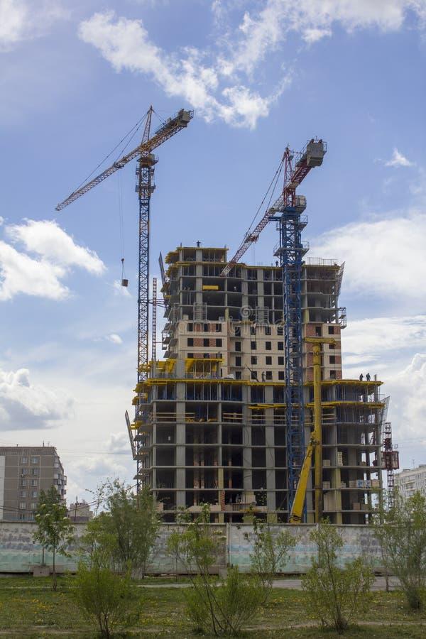 Δύο γερανοί πύργων κοντά σε μια σύγχρονη πολυκατοικία κάτω από την κατασκευή στοκ εικόνα με δικαίωμα ελεύθερης χρήσης
