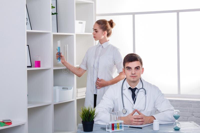 Δύο γιατροί, ο τύπος κάθονται στον πίνακα, και το κορίτσι εξετάζει την μπλε υγρή φιάλη στοκ εικόνα με δικαίωμα ελεύθερης χρήσης