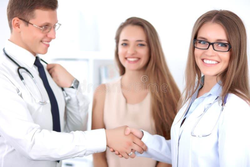 Δύο γιατροί που τινάζουν τα χέρια ο ένας στον άλλο ενώ ασθενής που στέκεται πλησίον στοκ εικόνα με δικαίωμα ελεύθερης χρήσης