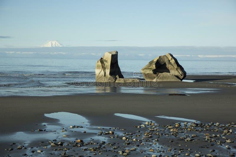 Δύο γιγαντιαίοι βράχοι σε μια μαύρη παραλία άμμου στοκ εικόνες