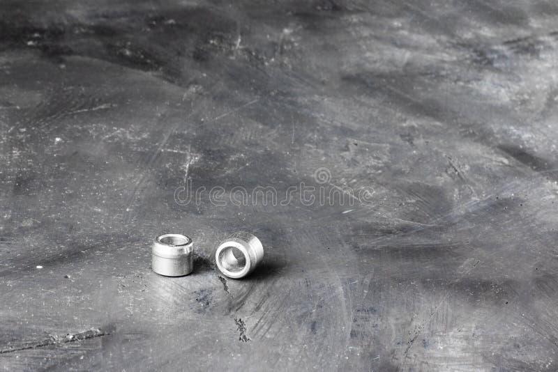 Δύο γκρίζα καρύδια ποταμών μετάλλων και clinch μπουλόνια στο αριστερό μέρος του στενόμακρου οριζόντιου πυροβολισμού στο υπόβαθρο  στοκ φωτογραφία