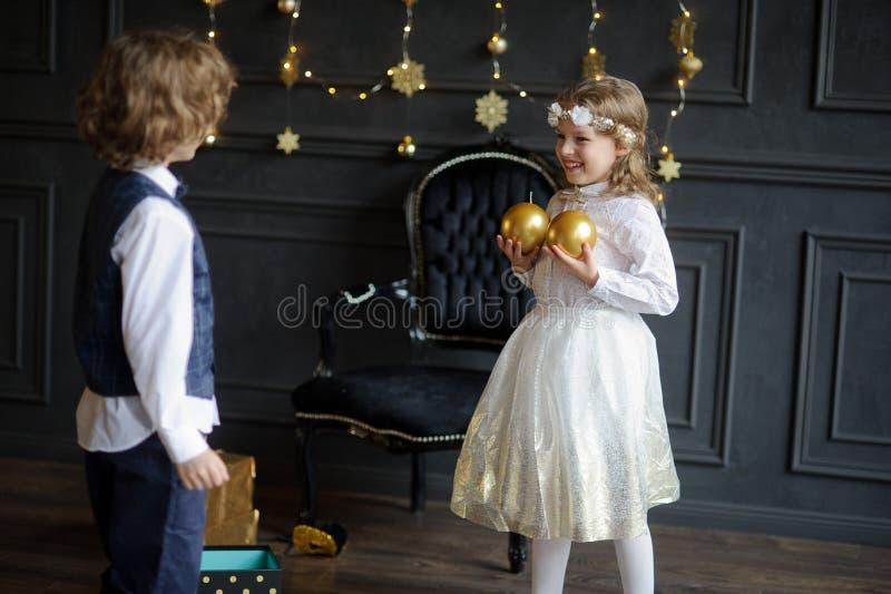 Δύο γοητευτικά παιδιά χαίρονται στα δώρα Χριστουγέννων στοκ φωτογραφία