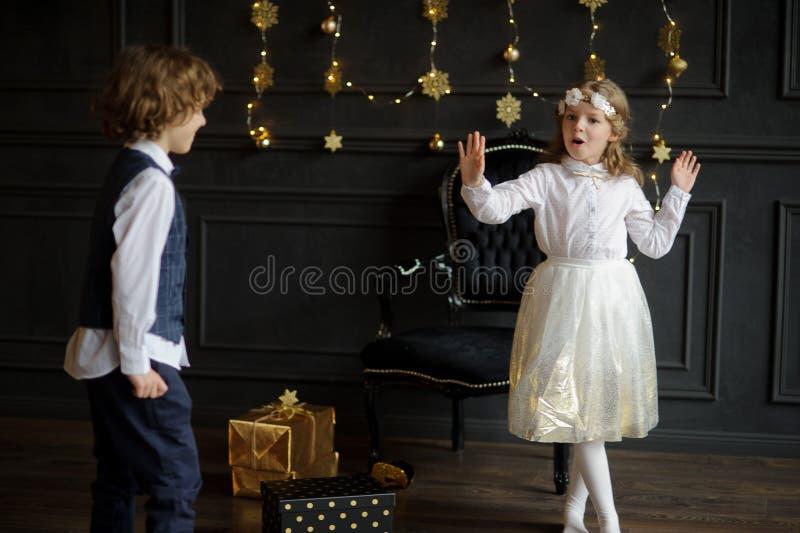 Δύο γοητευτικά παιδιά χαίρονται στα δώρα Χριστουγέννων στοκ φωτογραφία με δικαίωμα ελεύθερης χρήσης