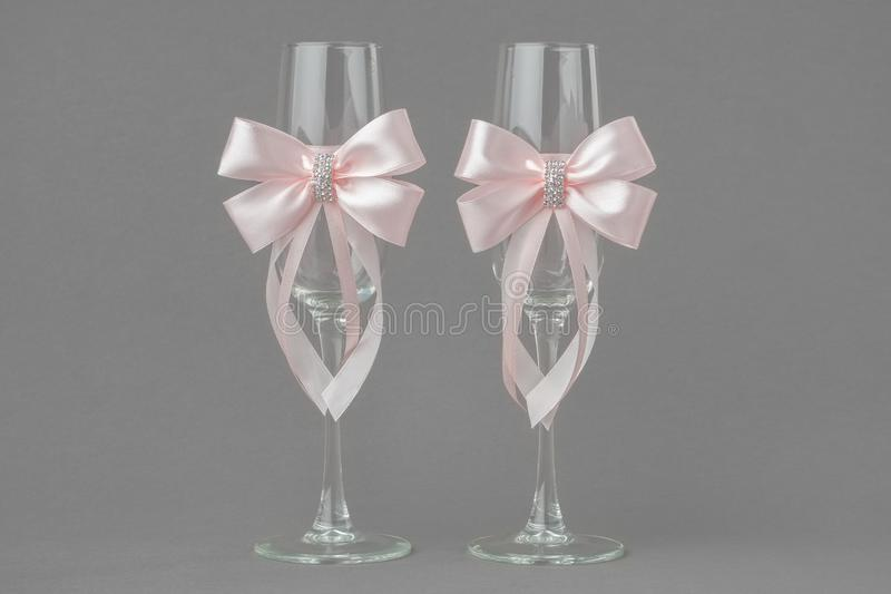 Δύο γυαλιά γαμήλιου κρασιού που διακοσμούνται με τις ρόδινες κορδέλλες στοκ φωτογραφία με δικαίωμα ελεύθερης χρήσης