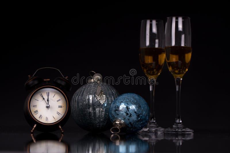 Δύο γυαλιά κρασιού με τις διακοσμήσεις σαμπάνιας, ρολογιών και Χριστουγέννων στοκ φωτογραφίες